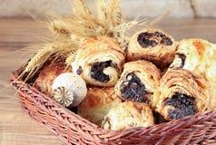 Os rolos doces com sementes de papoila encontram-se em uma cesta de vime Imagens de Stock Royalty Free