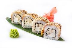 Os rolos excelentes e originais do sushi com enguia, omeleta e queijo de Philadelphfia apresentados em uma banana folheiam Isolad Fotografia de Stock Royalty Free