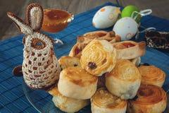 Os rolos pequenos franceses em um prato de vidro com mel em uma bacia de ovos e de Páscoa coloridos fizeram malha o coelho imagem de stock
