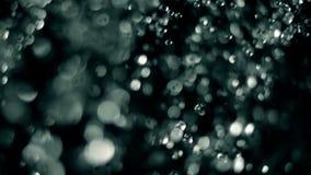 Os rops abstratos do waterd voam sobre o fundo escuro filme
