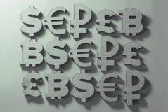 os símbolos do dinheiro e as moedas do mundo encontram-se em um fundo cinzento imagens de stock