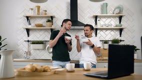 Os sócios alegres novos felizes que estão perto da mesa de cozinha são algo que fala e que come o café da manhã em casa na manhã filme