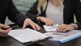 Os sócios comerciais discutem o contrato na tabela na empresa internacional video estoque