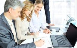 Os sócios comerciais estão discutindo um plano da cooperação na perspectiva do trabalho da equipe no escritório Imagens de Stock Royalty Free