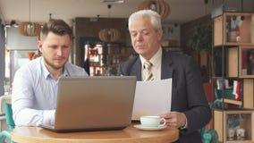 Os sócios têm a reunião de negócios no café video estoque