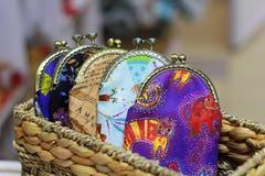 Os sacos coloridos para o dinheiro com um fecho do metal estão em uma cesta de vime imagens de stock