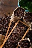 Os sacos da juta e os recipientes de madeira encheram-se com os feijões do cofee foto de stock royalty free