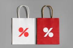 Os sacos de compras vermelhos e brancos de reciclam o papel com sinal de por cento no fundo cinzento Fotos de Stock