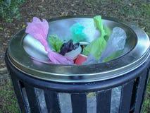 Os sacos de plástico desperdiçam no escaninho do metal fotografia de stock