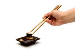 Os salmões rolam com o abacate nos chopsticks sob a placa Fotografia de Stock
