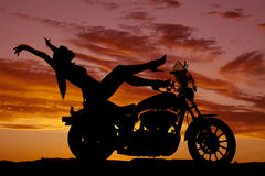 Os saltos da motocicleta da mulher da silhueta levantam as mãos para trás fotos de stock