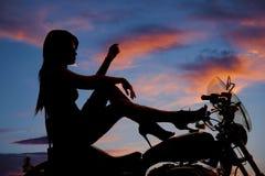 Os saltos da motocicleta da mulher da silhueta levantam o joelho da mão foto de stock