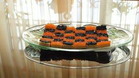 Os sanduíches com o caviar vermelho e preto alinharam sob a forma de um tabuleiro de xadrez Foto de Stock Royalty Free