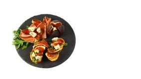 Os sanduíches com prosciutto, os figos frescos, o dorblyu e as bagas em uma placa do xisto são isolados em um fundo branco Vista  fotos de stock
