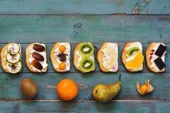Os sanduíches doces do fruto encontram-se em seguido em uma tabela verde de madeira velha Fruto e sanduíches em uma tabela rústic Imagem de Stock