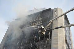 Os sapadores-bombeiros abordam uma chama em um bloco de escritório fotografia de stock