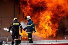 Os sapadores-bombeiros esforçam-se para extinguir o fogo que estoirou na foto de stock royalty free
