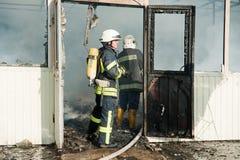 Os sapadores-bombeiros extinguem um grande fogo no mercado de Troyeschina com água e os extintores Fotografia de Stock Royalty Free