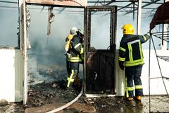 Os sapadores-bombeiros extinguem um grande fogo no mercado de Troyeschina com água e os extintores Foto de Stock Royalty Free