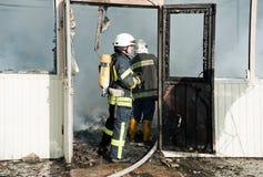 Os sapadores-bombeiros extinguem um grande fogo no mercado de Troyeschina com água e os extintores Fotografia de Stock