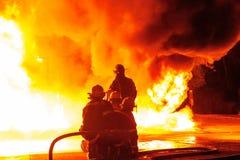 Os sapadores-bombeiros largos do ângulo no depósito alinham enfrentar o inferno quente branco com fumo billowing Imagem de Stock