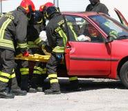 Os sapadores-bombeiros na ação e puxam ferido do carro Fotografia de Stock