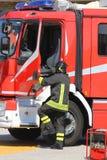 os sapadores-bombeiros na ação saltam para baixo rapidamente da viatura de incêndio du Imagens de Stock