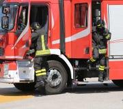 Os sapadores-bombeiros na ação saltam para baixo rapidamente do caminhão Fotografia de Stock Royalty Free