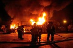 Os sapadores-bombeiros no depósito alinham enfrentar o inferno quente branco com fumo billowing Imagem de Stock