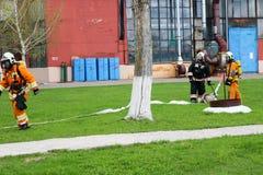 Os sapadores-bombeiros profissionais, os salvadores em ternos à prova de fogo protetores, os capacetes e as máscaras de gás são p imagem de stock