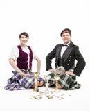 Os Scottish de dança da mulher e do homem dançam com copos e medalhas Fotografia de Stock