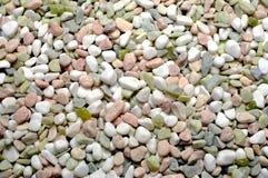 Os seixos cor-de-rosa, brancos e verdes cobrir o fundo Imagem de Stock
