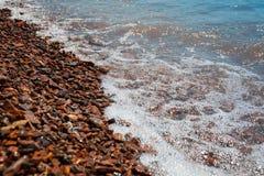 Os seixos marrons brilhantes do mar cobertos com acalmar-se acenam imagem de stock royalty free