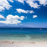 Os seixos perfeitos encalham e céu azul com nuvens Fotografia de Stock
