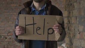 Os sem abrigo com ` da placa ajudam o ` vídeos de arquivo