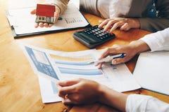 Os serviços dos bens imobiliários para a casa de compra guardam o modelo da casa e o pagamento da tabela de cálculo ao cliente imagem de stock