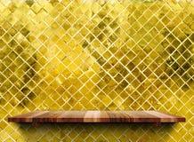 Os shelfs de madeira vazios na telha lustrosa do ouro de mosaico muram, zombam acima do tem fotos de stock royalty free