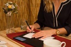 Os sinais da mulher creditam o recibo do cartão no restaurante fotografia de stock