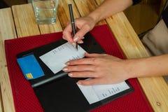 Os sinais da mulher creditam o recibo do cartão no restaurante fotos de stock