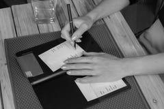 Os sinais da mulher creditam o recibo do cartão no restaurante foto de stock royalty free