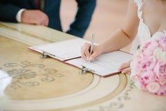 Os sinais da noiva no registro no documento no dia do casamento imagem de stock