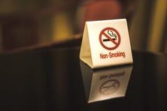 Os sinais de aviso que proibem o fumo na tabela Imagens de Stock