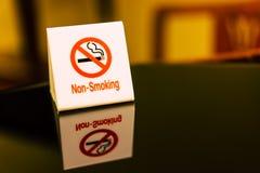 Os sinais de aviso que proibem o fumo na tabela Fotos de Stock Royalty Free