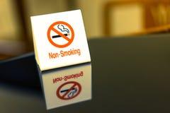 Os sinais de aviso que proibem o fumo na tabela Imagem de Stock Royalty Free