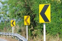 Os sinais de estrada amarelos advertem motoristas para adiante a curva perigosa Imagens de Stock