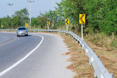 Os sinais de estrada amarelos advertem motoristas para adiante a curva perigosa Imagens de Stock Royalty Free