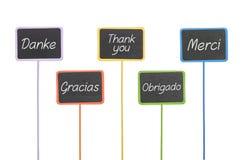 Os sinais com o texto agradecem-lhe em línguas diferentes Fotos de Stock