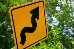 Os sinais de tráfego da bicicleta para a estrada curvam-se adiante Fotos de Stock Royalty Free