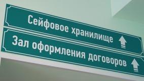 Os sinais plásticos verdes no texto do russo da parede dizem o depósito e a sala de reunião seguros filme