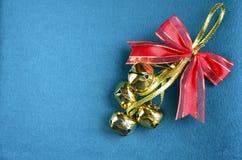 Os sinos de Natal com a fita vermelha no azul sentiram o fundo Decoração do Natal Imagens de Stock Royalty Free